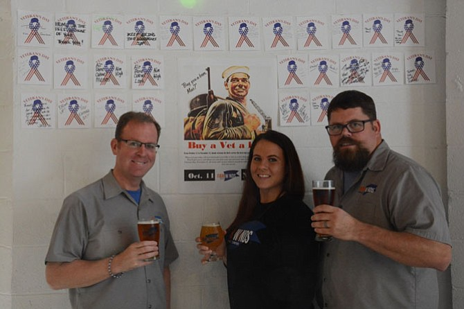 From left, Fair Winds Brewing Company CEO Casey Jones, tasting room manager Jacquelyn Olejniczak and brand ambassador Mike Kuykendall in front of the brewery wall holding 'Buy a Vet a Beer' notes.