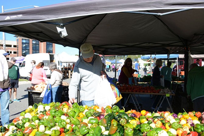 Zoran Duric of Fairfax chooses among a vibrant assortment of peppers from Santa Cruz Produce in Montross, Va. at the Burke Farmers Market on Oct. 15.