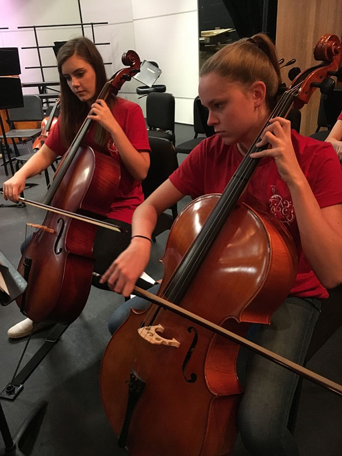 Members of the Symphonic Orchestra warm up before the performance as students from Thoreau MS filled the auditorium.