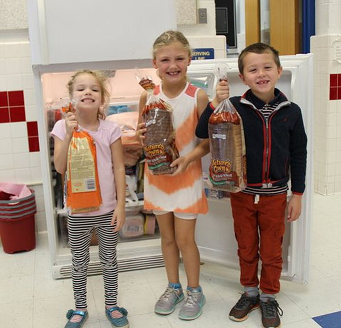 Churchill Road first graders Zara Lang, Skyler Jones and Ean Munn were eager to make sandwiches for Martha's Table from the sandwich fixings donated by the community.