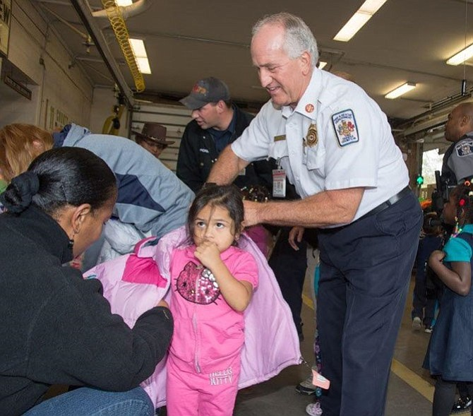 Fairfax County Fire Chief Richard  Bowers helps a child with a coat during the Firefighters and Friends annual coat distribution day Oct. 27 at Penn Daw Station 11. More than 1,600 new coats and over 500 new books were distributed to 70 schools, shelters and nonprofits in Fairfax County and Alexandria.