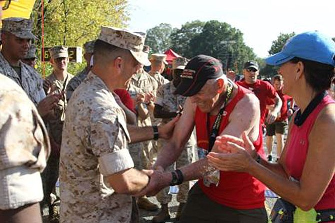 Al Richmond, center, is congratulated  by Quantico base commander Col. Joseph M. Murray after completing his 41st consecutive Marine Corps Marathon Oct. 30 in Arlington. The 77-year-old Maywood resident is the only individual to complete every MCM since its inception in 1976. He completed the course in 6:39:47.