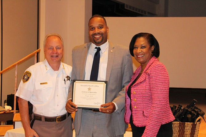 Kristopher Futrell (center) receives a certificate of appreciation from Sheriff Dana Lawhorne (left) and Lavern Chatman.