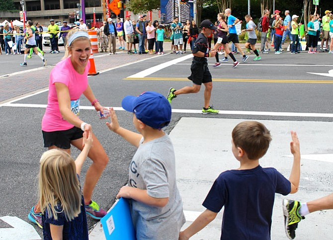 Cara Donley gets high-fives from her niece and nephews as she runs through Crystal City during the Marine Corps Marathon Oct. 30. Donley, 26, completed the 26.2-mile course in 3:26:16, placing 70th among all female runners.