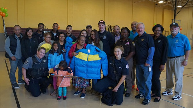 Volunteers from Alexandria's police, fire, sheriff's and recreation departments gather Oct. 29 during the annual Firefighters and Friends coat distribution day at the Charles Houston Recreation Center. More than 300 adult and children's coats were given to families from across the city.