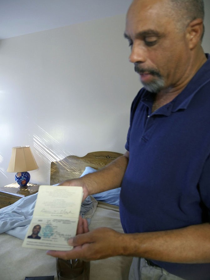 "Dennis Clark pulls out an outdated passport from 1993-95 when his wife was a diplomat in Venezuela. He says, ""I went a long way from being the husband of a diplomat to living on the streets on Columbia Pike. And now I have my own home."""