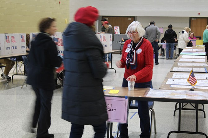 Election Official Mary Satian, a volunteer, helps voters get in line for the correct precinct at Langley High School.