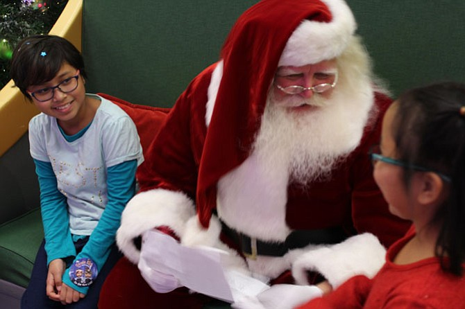 Althea Miedzinski, 9 (left), and her sister Zaira Miedzinski, 7 (right), show Santa Claus their wish list.