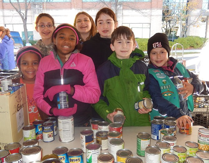 Sorting canned goods last year are members of Girl Scout Troop 3327 of West Ox Baptist Church in Chantilly.