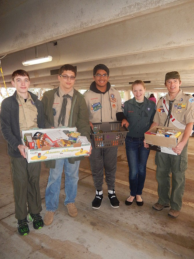 Transporting donated food within the sorting area are members of Boy Scout Troop 1826 of Chantilly. From left are Nathan Goehring, Brigham Hampton, Mosiah Santiago, Stacia Bangerter and Mark Wilkinson, one of the troop leaders.
