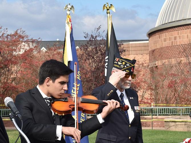 Violinist Joseph Letteri,  South Lakes High School Senior, plays the National Anthem while Bob Thompson, 1st Vice Commander, American Legion Post 184, Herndon/Reston, renders a salute.