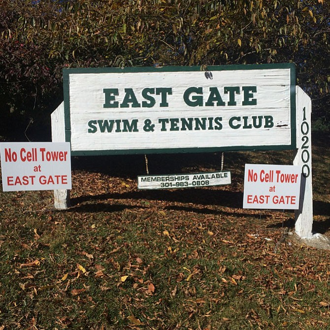 Protest signs are affixed to the East Gate Swim and Tennis Club sign.