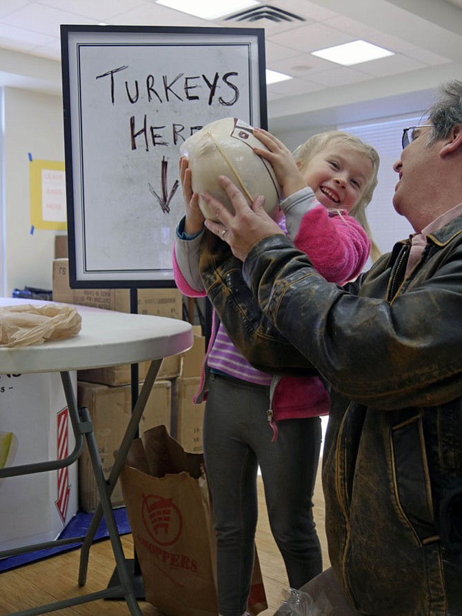 Six-year-old Maggie Rinzel struggles through the door of the Ministry House at Our Lady Queen of Peace Church with a turkey. Maggie and her dad, Dan, are dropping off their turkey donation for the 239 families who have registered to receive a turkey dinner. The church is located on 19th Street S in Arlington.