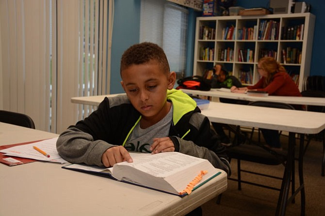 On a weekday afternoon, young Fairfax resident Demetrius Dowling works independently on an extra math word problem.
