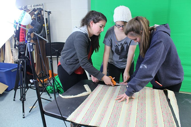 Junior Sarah McDonald, 16 (left), freshman Maddy Rubin, 14 (middle), and junior Amelia Patton, 16 (right), cut fabric to reupholster the seats of chairs used in the show.