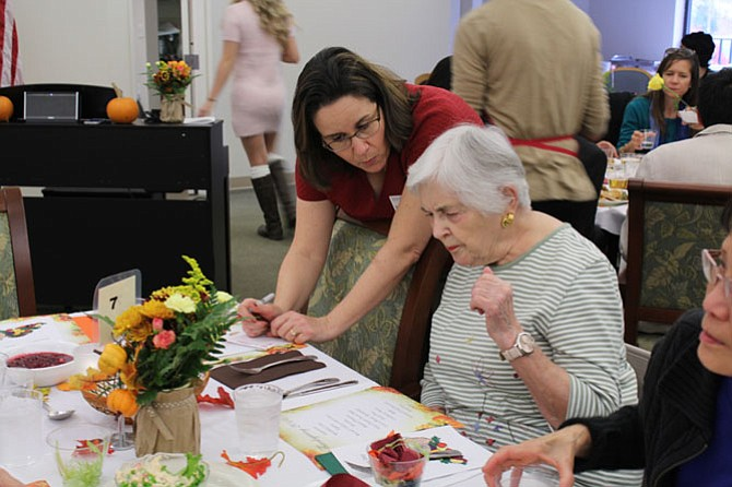 """Marcia Cottros, member of the Lewinsville Presbyterian Church, takes a guest's order. She has been helping serve food at the dinner for the last four years. """"It's something I like doing every year,"""" she says. """"I wouldn't miss it."""""""