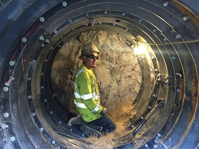 A CRC worker kneels in the tunnel where he is hand mining to carry utilities to and from the Silver Line Phase 2.