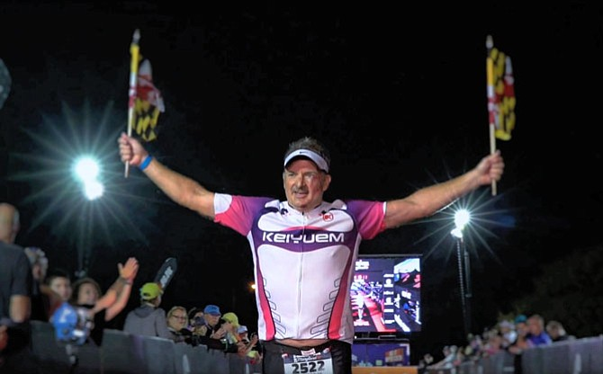 "Coming up to the ""gauntlet"" home stretch, Bill Vitaletti of Springfield grabbed a pair of Maryland state flags and unfurled them as he ran across the finish of his first Ironman triathlon."