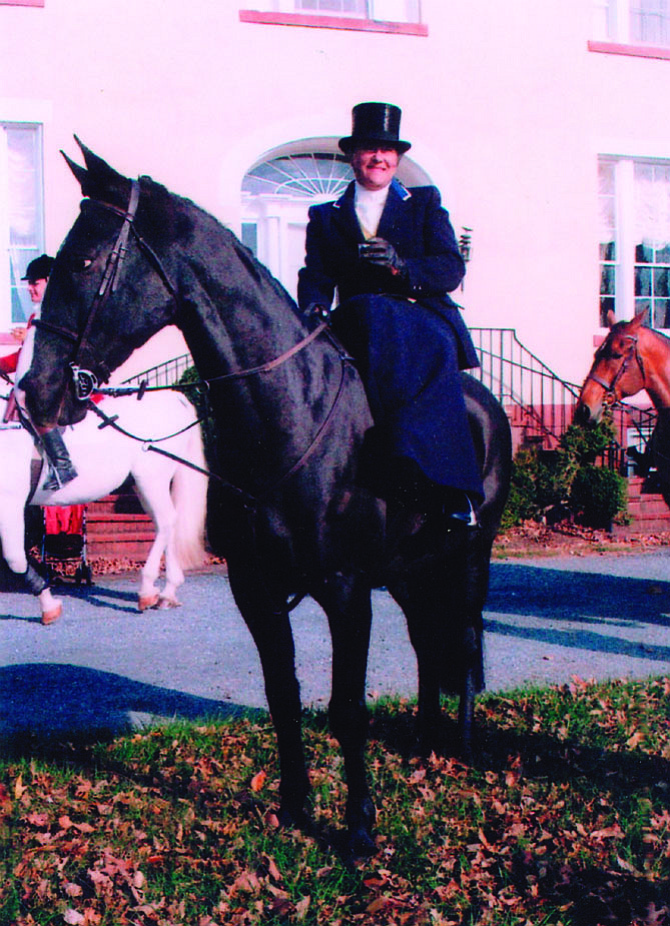 "Potomac Hunt member Sarah O'Halloran, one of the few hunt members who ride side-saddle, is in formal hunting attire for the annual Thanksgiving Day hunt with her mount ""Jeeves."""