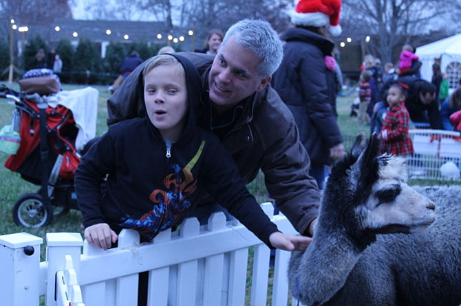 Freedom Hill Elementary School student Evan Fowler, 11, and his dad Geoff Fowler pet an alpaca at the petting zoo during the Celebration of Lights.