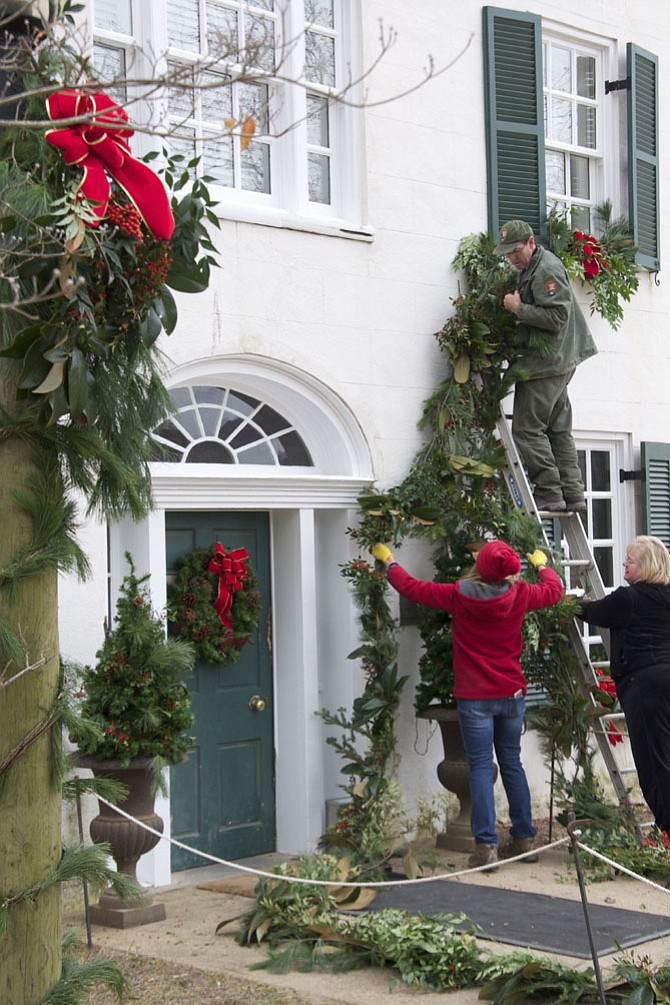 Members of the Little Falls Garden Club are assisted by C&O Canal National Historical Park staff in their holiday decorating of the Great Falls Tavern Visitor Center.