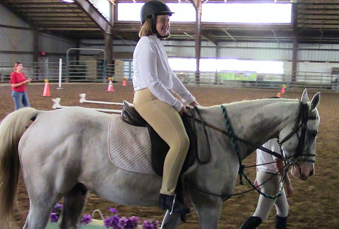 Nicole Springer rides a horse named Max at the SPIRIT Equestrian Program.
