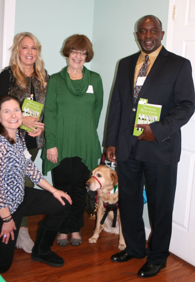 """From left: Danielle Houston Karst (kneeling), Molly Raymond, Toni Popkin, Bud (Popkin's service dog) and Derek O'Neal at the November launch of """"Surviving Brain Injury"""" hosted by Brain Injury Services."""