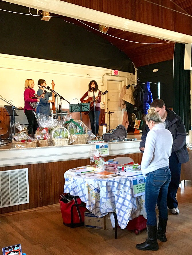 The Stewart Sisters play Americana music while Alex Brudno explains the various Great Falls Historical Society gift possibilities, including gift baskets, publications, postcards, or our latest, Thelma's Country Store, A Colvin Run Road Legacy, in its second printing.