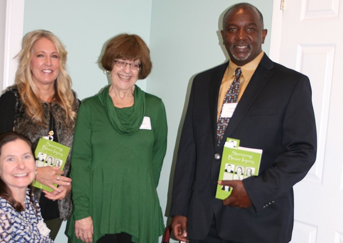 "From left: Danielle Houston Karst (kneeling), Molly Raymond, Toni Popkin, and Derek O'Neal at the November launch of ""Surviving Brain Injury"" hosted by Brain Injury Services."