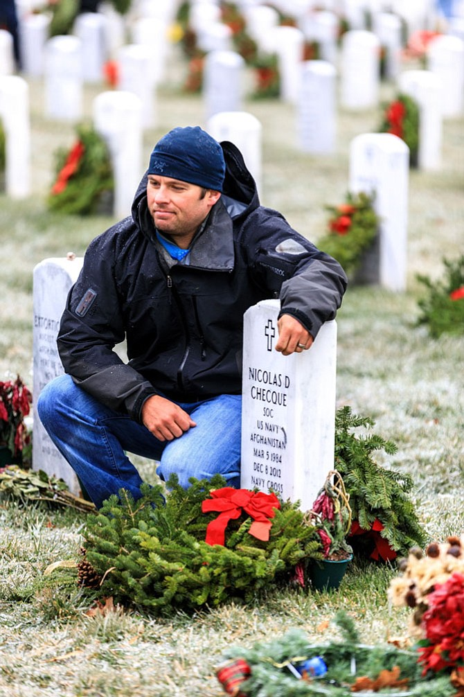 Navy SEAL and Medal of Honor recipient Ed Byers kneels next to the headstone of Nicolas Checque, a friend who was killed in 2012 in the same fight where Byers earned his Medal of Honor. Byers joined volunteers from Wreaths Across America Dec. 17 in placing more than 245,000 wreaths to honor the veterans buried at Arlington National Cemetery.