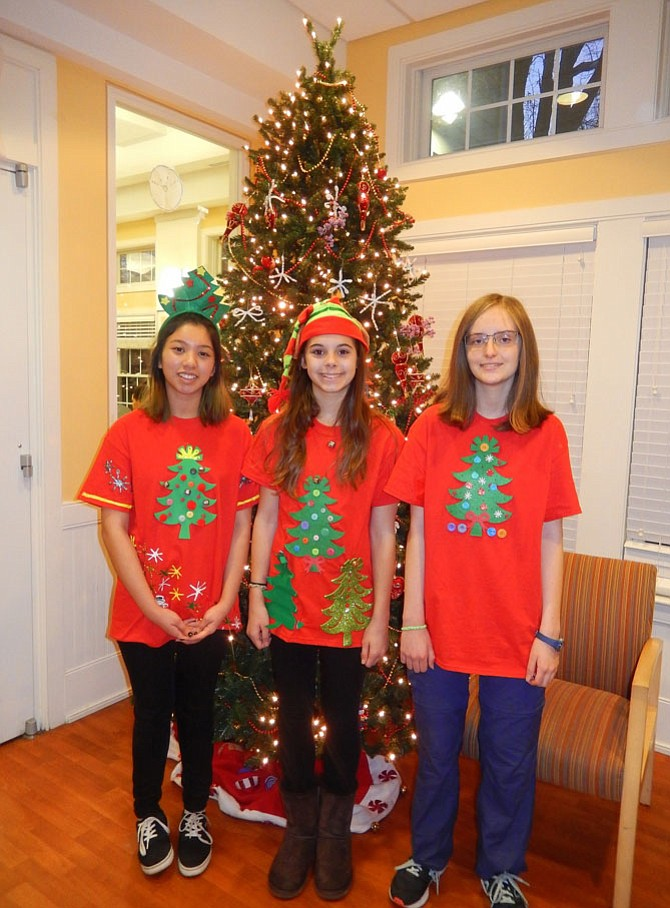 Standing in front of the shelter's Christmas tree are (from left) Chantilly High freshmen Kimberly Nguyen, Emma Tilley and Megan Sweeney.