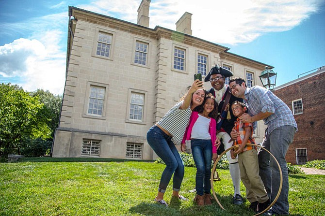 Family takes a selfie with Town Crier Ben Fiore-Walker outside the Carlyle House.