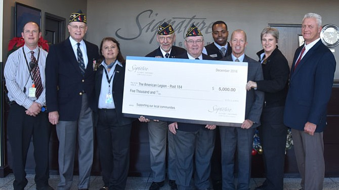 Daniel Gillespie, Robert Thompson and David Kirby of The American Legion  Wayne M. Kidwell  Post 184 accept a $5,000 donation check from Signature Flight Support, a BBA Aviation Company. Pictured, from left:   Wesley Lowery, Signature Flight Support; Daniel Gillespie, Post 184 Finance Office; Parwin Kurasz, Signature Flight Support, Robert Thompson, Post 184 1st Vice Commander; David Kirby, Post 184 Commander; Jean Best, Robert Grant, Katrin Phillips, and Tony Wright (Signature Flight Support).