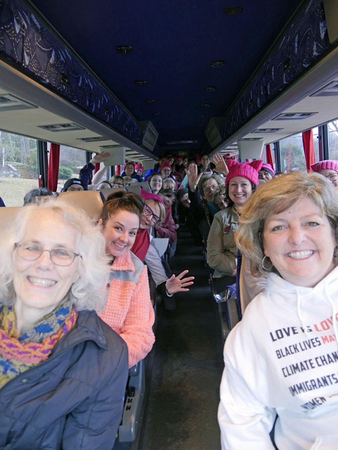 """Amidst a light drizzle on Saturday morning, a bus full of Arlingtonians and out-of-town friends and relatives leaves from Rock Spring UCC at 9 a.m. Signs are crammed between seats and the demand for pink """"pussy"""" hats is greater than the supply. The Rev. Kathy Dwyer, front right, grabs the microphone """"just like in church"""" and gives announcements """"just like in church"""" on the return trip, the buddy system and how to text her any changes in plans."""