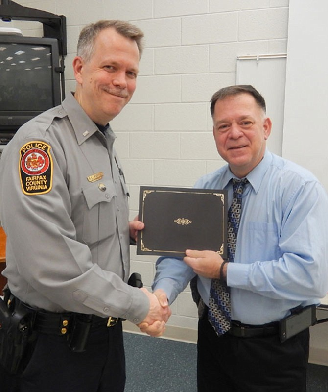 1st Lt. Alan Hanson (left), assistant commander of the Sully District Station, presents the Officer of the Month certificate to Det. Steven Kitzerow.