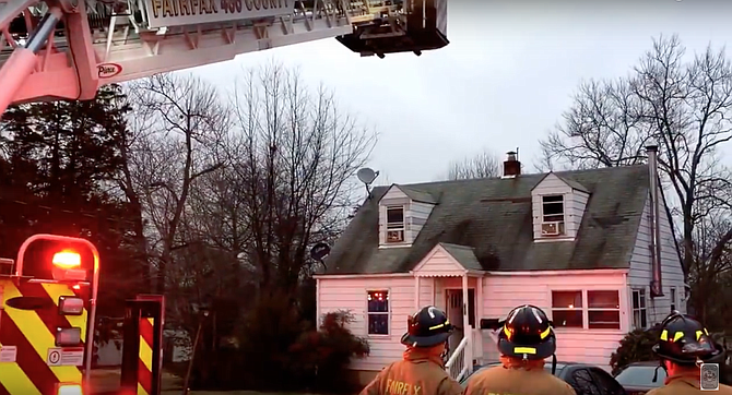 Firefighters used a ladder to get a fire hose to the second-floor attic to extinguish the fire.