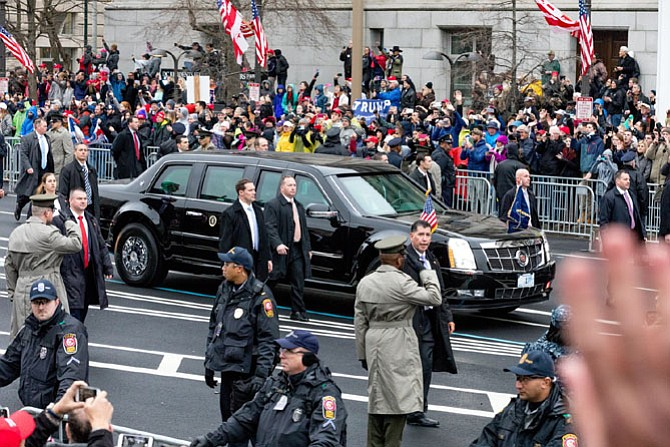 Fairfax County police officers, in foreground, provide security to President Donald Trump's limousine as it makes its way through the streets of Washington during the Inauguration Day parade Jan. 20. More than 3,000 officers from across the country were sworn in to assist with Inauguration activities, including 105 officers from the Fairfax County Police Department.