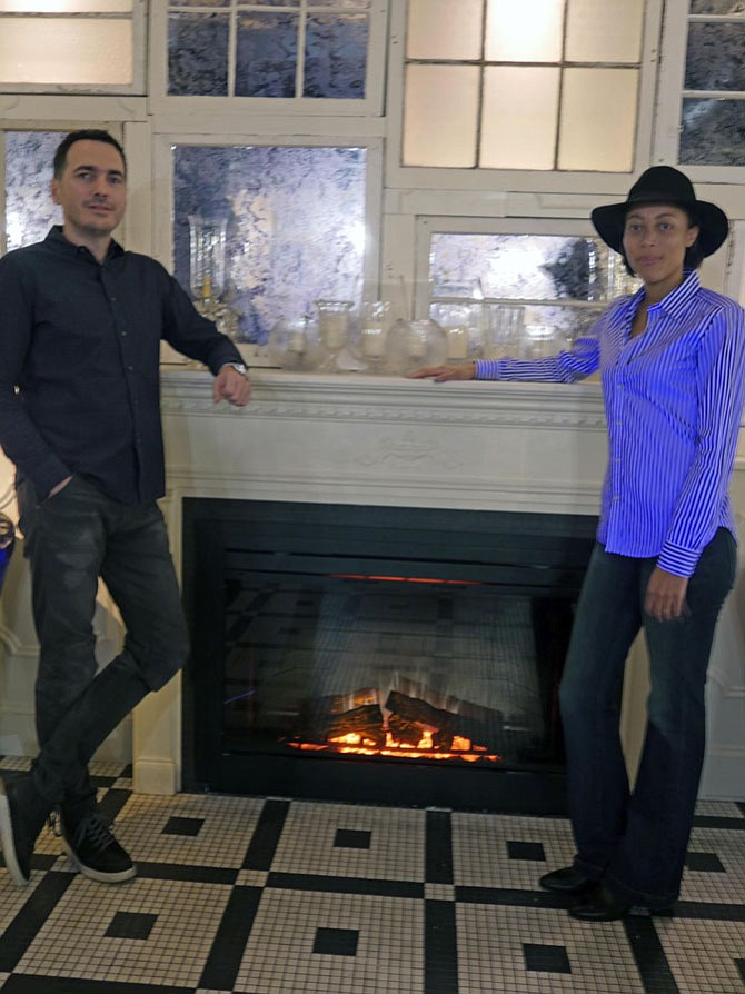 Ivan Iricanin and his wife Nya Gill stand before the fireplace meant to create a warm and cozy space in BABA, a new neighborhood gathering spot. He explains that BABA means grandmother in Serbian, and it is cozy and warm, just like memories of your grandmother.