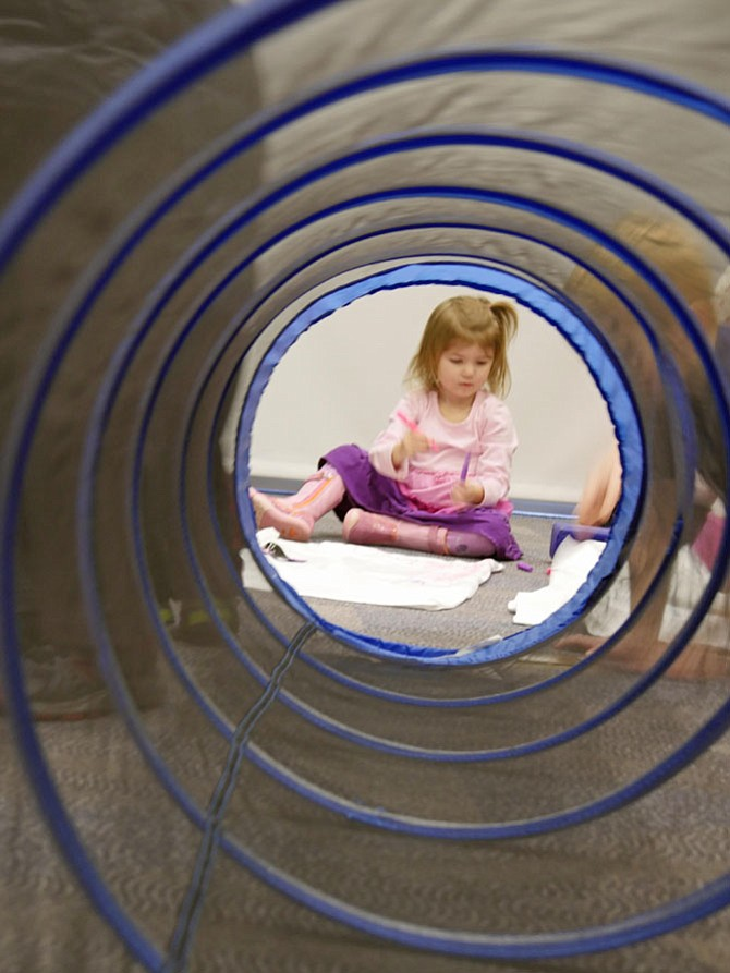 Cora Sehardt, 2 and a half years old, sits on the floor at the end of the crawl-through tunnel that is part of the obstacle course for the Superhero Training Day at Shirlington Library.  She sits amidst a room full of K-5th graders attending the Jan. 31 event.