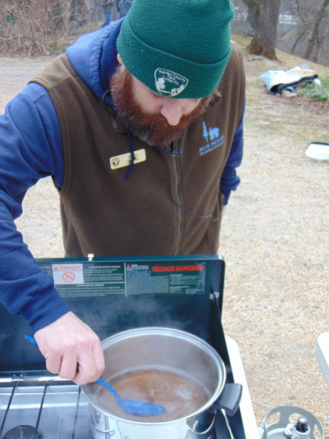 Steve Golobic, an Assistant Miller at Colvin Run Mill in Great Falls, stirs a batch of boiling sap from a maple tree during a Maple Syrup Boil Down talk on Sunday, Feb. 5, 2017.