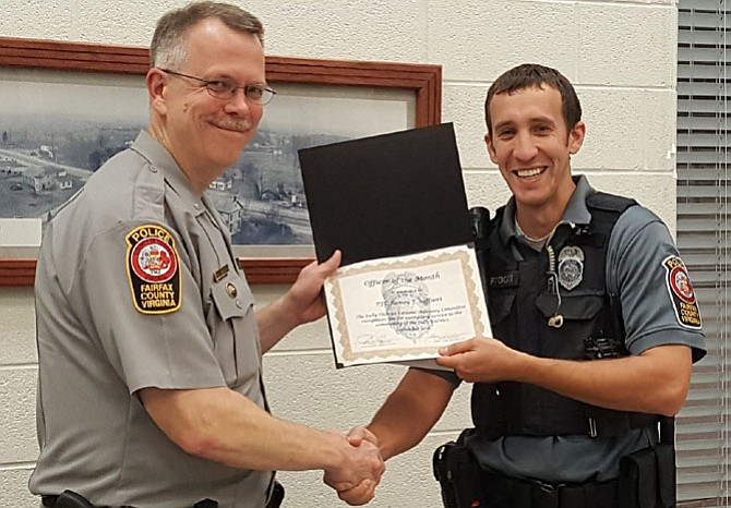 Assistant Station Commander Alan Hanson (left) gives PFC Ramsy Saffoori his Officer of the Month certificate.