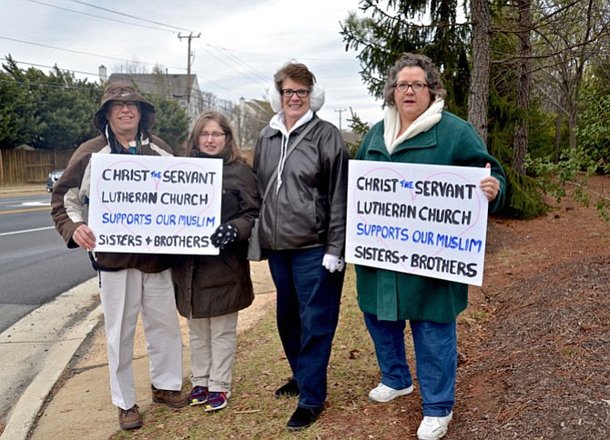 "From left -- Bruce Bailey of Centreville, Julia Persing of Reston, Janet Rider of Centerville and Jolene McNamara of Herndon, all members of Christ the Servant Lutheran Church in Reston, show their support for their ""Muslim brothers and sisters"" at the entrance to the ADAMS Center during the Friday Peace Rally."