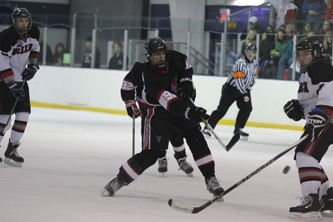 Forward Luke Pohlman threads a shot between the McLean defense towards McLean's net. The Warhawks secured the division title with their 4-3 win over McLean. Pohlman scored two goals.