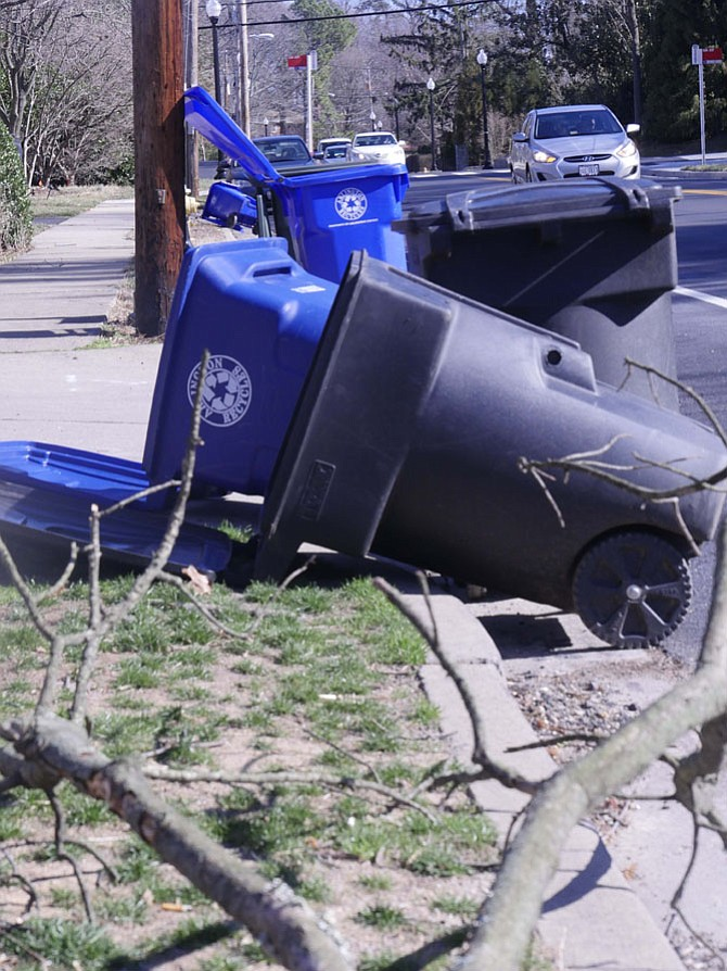 Garbage cans blown over by gusts of strong winds line Old Dominion Drive on Monday morning, Feb. 13. Wind gusts were reported to have been up to 50 mph during the night.