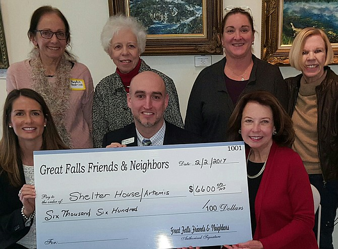Artemis House Executive Director Joe Meyer and Director of Development Jennifer Delessio [front row left] accept the donation from the Great Falls Friends and Neighbors, surrounded by members of the organization. The funds were raised through the club's annual White House Ornament holiday fundraiser.