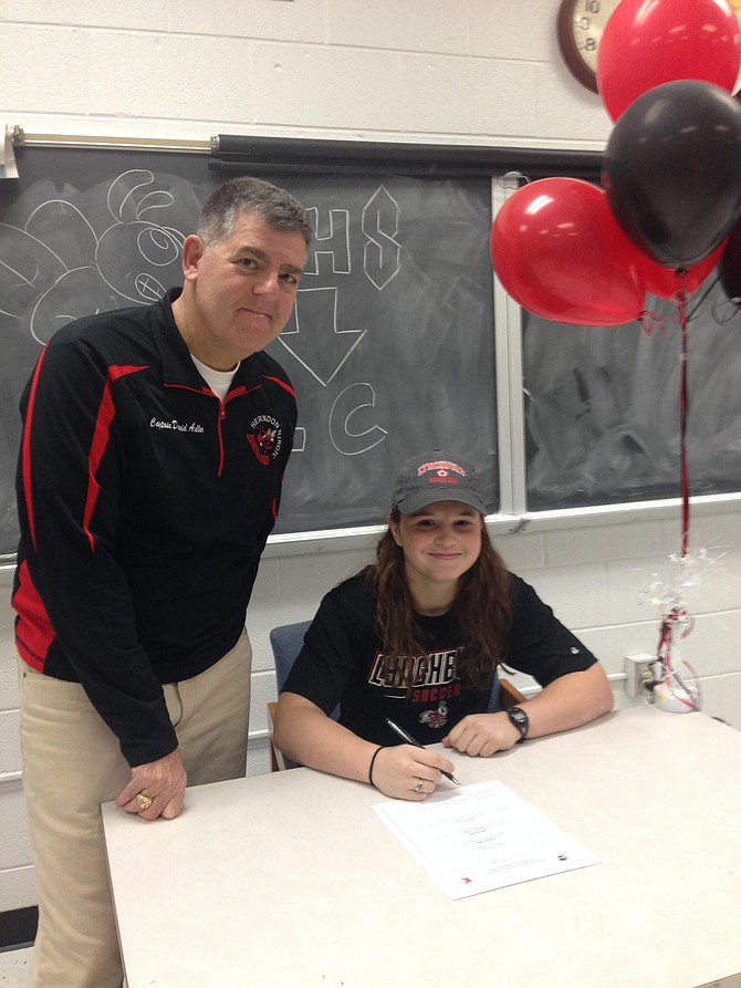 Bea Kelly-Russo and Cpt. Adler signing the intent form for Lynchburg College Women's Soccer.