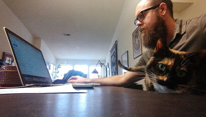 Connection Newspapers community reporter Tim Peterson doesn't always work at a desk, but when he does, one roommate's calico, Sassy Chupacabra often likes to oversee editorial operations.