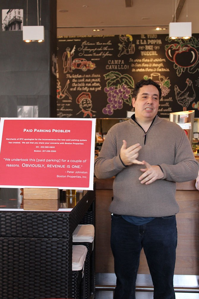 "Aaron Gordon of Gordon Food Group and the proprietor of the Red Velvet Cupcakery on Democracy Drive, is one of the merchants who is leading the charge against Boston Properties. He encouraged all the merchants to display this red sign in their windows, which says, ""Paid Parking Problem: Merchants of RTC apologize for the inconvenience the new paid parking system has created."""