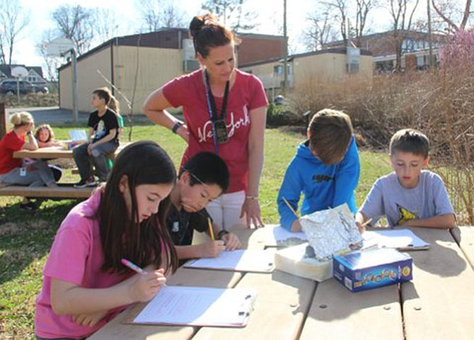 Churchill Road third graders in Carrie Banfield's class are learning about renewable energy.  They built solar ovens, then created hypotheses as to whether or not the sun could heat and melt chocolate for s'mores. Third graders Macey Warshaw, Ben Huang, Jack Cunha-Mendonca and Ellis Farah work with their teacher, Banfield, in the outdoor classroom.