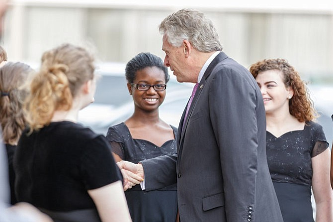 Gov. Terry McAuliffe (right) meets with members of the Robert E Lee High School Chorus at the opening of the new veterans services office in Springfield on Feb. 22.